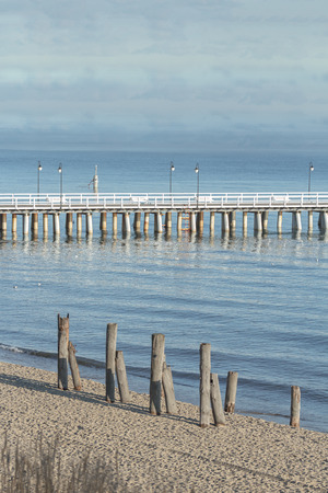 lifeboat station: Wooden walking sea Gdynia Orlowo Pier with old foundation piles on coast in Baltic Poland