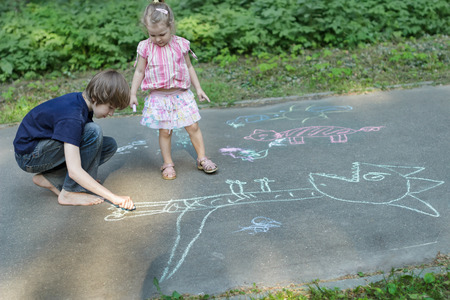 exhilarated: Sibling children are sharing sidewalk chalks and drawing on asphalt surface