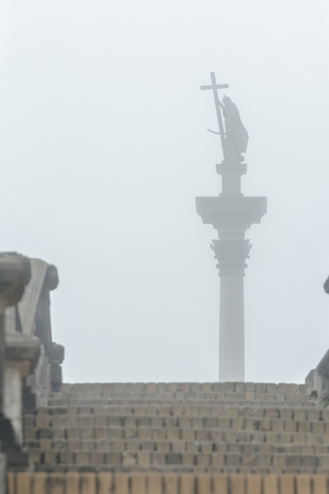 'dark ages': Capital city landmark Sigismunds Column and statue silhouette in fog view from stone stairs in Polish Warsaw