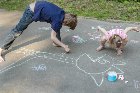 exhilarated: Sibling children are playing during sidewalk chalking on asphalt surface Stock Photo
