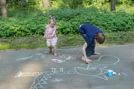 exhilarated: Sibling children are having fun during sidewalk chalking on asphalt surface