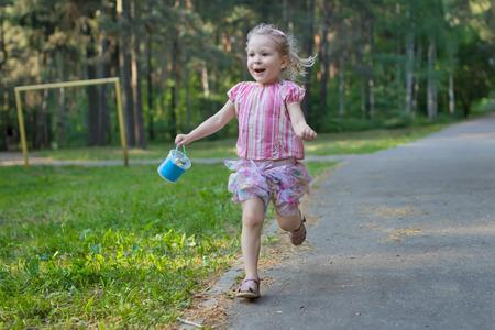 exhilarated: Exhilarated running girl on asphalt park footpath is holding package of sidewalk chalks