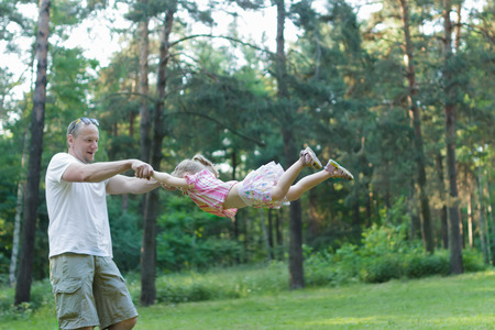 exhilarated: Happy father is spinning around his daughter in green summer park outdoors