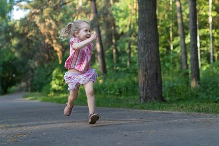 three years old: Exited three years old runner girl on asphalt park footpath is holding piece of sidewalk chalk