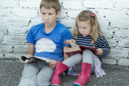 Wondering sibling children are sitting on asphalt ground with books in hands