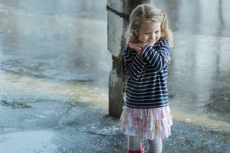 Happy surprised girl with pink barrette in blonde wavy hair is clapping in joy and holding her hands by cheek at rainy background