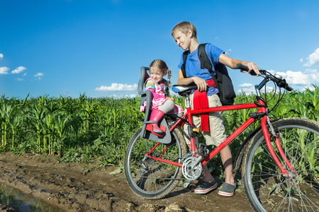 sibling: Sibling teenage boy is cycling with his little sibling sister on baby bike seat on farm corn field dirt road
