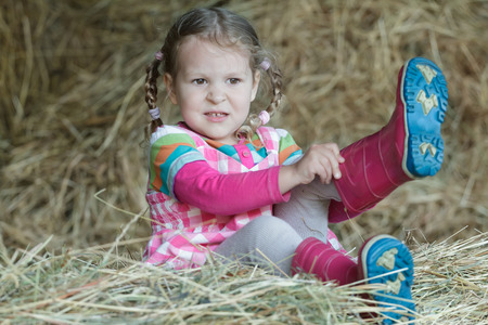 Little braided girl is putting on red gum boots on dried loose grass hay in farm haystack Stock Photo