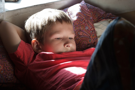snění: Resting and reading teenage boy is wearing red t-shirt in backlit