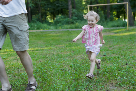Laughing little daughter is running after her father in summer park outdoors
