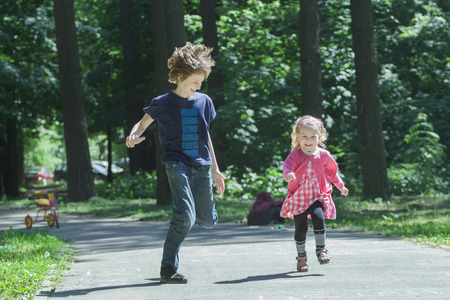 exhilarated: Laughing sibling children are playing tag and running on park asphalt footpath Stock Photo