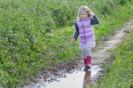 Smiling blonde girl with loose fair hair is walking on dirt road rain puddle on purple clover flowers meadow