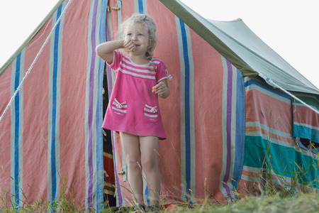 Blonde little camper girl is relaxing near striped vintage canvas tent