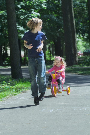 exhilarated: Laughing sibling sister is chasing after her brother on pink and yellow kids tricycle