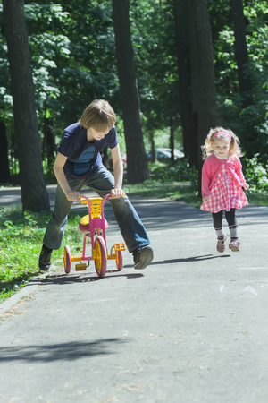 sibling: Sibling children are playing tag game by running and riding kids tricycle Stock Photo