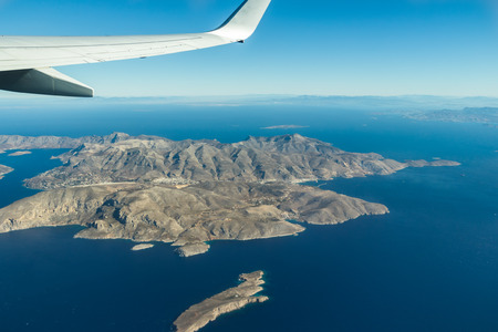 Birds-eye view of Greek Kalymnos island of Dodecanese archipelago and Aegean sea from plane window with wing