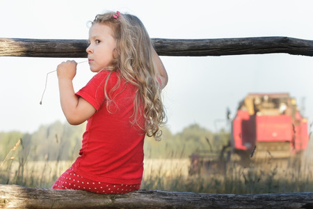Perching girl is watching over working combine harvester