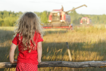 Blonde farm girl in red polka dot kids pans is looking at field with reaping combine harvester