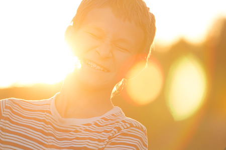Headshot portrait of screwing up eyes and laughing teenage boy in warm sunset backlit with lens flares Stock Photo
