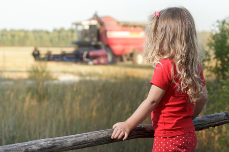 Sitting spectator girl is watching over working combine harvester Stock Photo