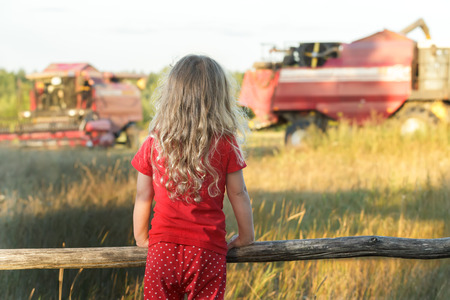 Little farm girl is wearing red polka dot kids pans looking at field with working combine harvesters