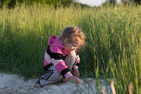 squatting down: Hunkering little girl is playing in field dirt outdoors at natural green meadow grass backdrop