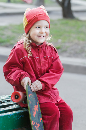 Laughing little girl is holding skateboard and sitting on green wood bench