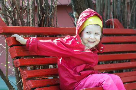 leaning forward: Laughing little girl is leaning forward and sitting on red rest wood bench