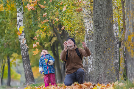 2 november: Smiling father with laughing daughter are tossing up yellow autumn leaves in park outdoors