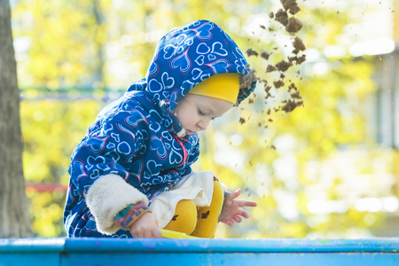 Little girl is playing in sandbox outdoors at autumn yellow shrubbery and trees leaves background Stock Photo