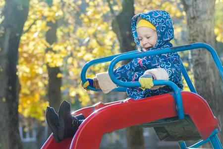 sit down: Muchacha de risa en la chaqueta con capucha caliente se desliza hacia abajo rojo de diapositivas de plástico patio de recreo en el otoño de hojas de los árboles de color amarillo de fondo
