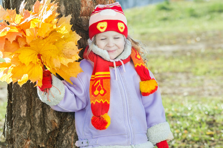 Smiling little girl is holding yellow with orange autumn leaves bunch in hand outdoor portrait