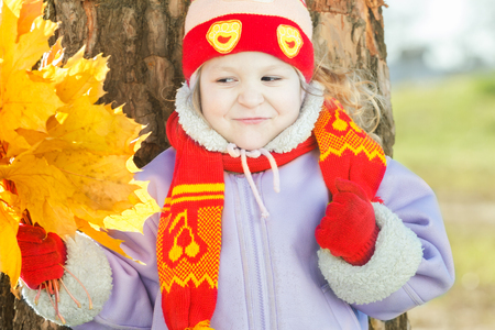 Little girl is holding yellow with gold autumn leaves bunch in hand outdoor portrait