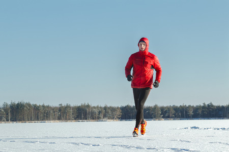training session: Running man is wearing red protective sportswear on winter training session outdoors
