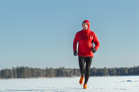 Ultra trail runner wearing red protective sportswear on winter training session outdoors Stock Photo