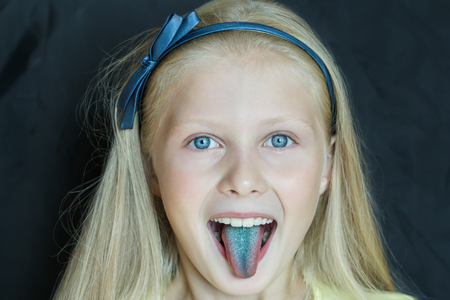 Close-up portrait of teenage blonde girl with sticking out blue tongue