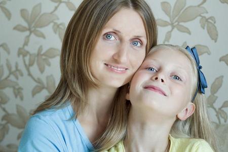 alice band: Family portrait of happy mother with her blonde teenage daughter Stock Photo