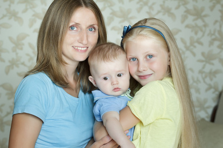 tres miembros felices que abrazan la familia posando para el retrato en interiores