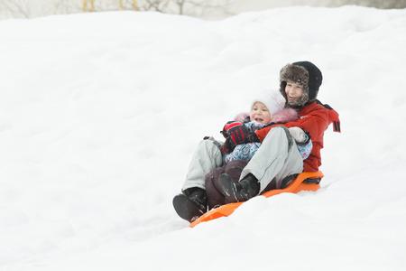 Happy siblings having downhill fun on winter orange plastic snow slider outdoors Stock Photo