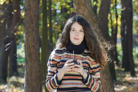 skivvy: Young woman is wearing knitted snowflakes pattern woolen sweater and holding hot yerba mate drink