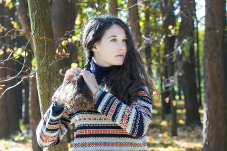 skivvy: Young woman in knitted woolly sweater is making braid Stock Photo