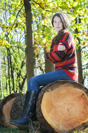 skivvy: Freezing woman sitting on sawn tree trunk and is hugging herself Stock Photo