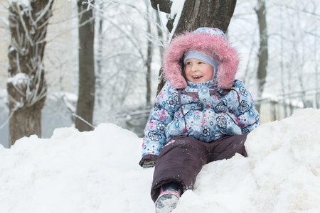 Winter outdoor portrait of laughing little girl is sitting on top of snow hill