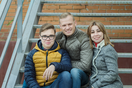 Family of three hugging people sitting on metal stairs at brick city building background