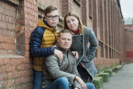 Family of three street urban portrait at red brick building wall background Stock Photo