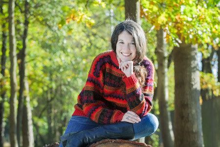 sawn: Outdoor portrait of cheerful young woman is sitting on sawn tree trunk