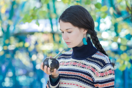 Woman wearing knitted snowflakes pattern sweater and turquoise earrings is drinking hot yerba mate Archivio Fotografico