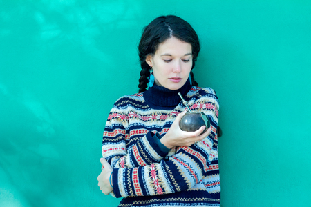 skivvy: Woman wearing woolen snowflakes pattern sweater and turquoise earrings is drinking hot yerba mate