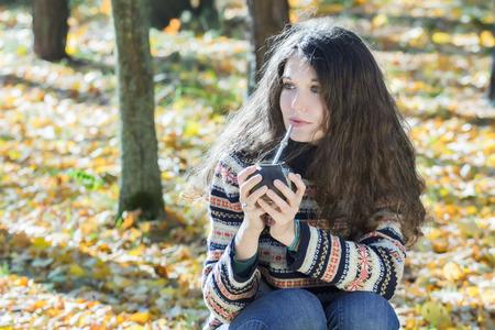 yerba mate: Mujer joven en el suéter de punto copos de nieve patrón de lana es beber la yerba mate caliente Foto de archivo
