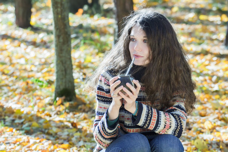 skivvy: Young woman in knitted snowflakes pattern woolen sweater is drinking hot yerba mate
